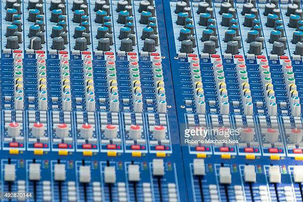 Closeup of an audio mixing console It has numerous knobs buttons and sliders A mixing console is an electronic device for combining routing and...