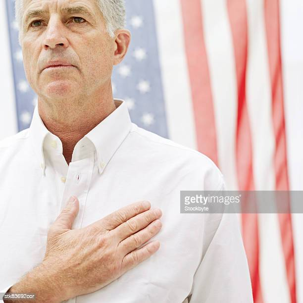 close-up of an elderly man standing with a hand on his heart in front of the American flag