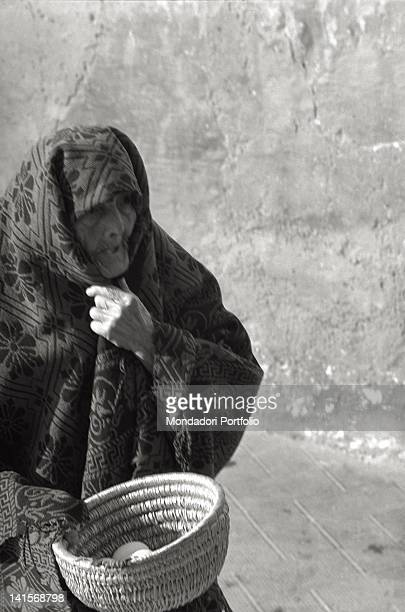 Closeup of an elderly woman from San Giovanni Rotondo holding a basket of eggs Italy