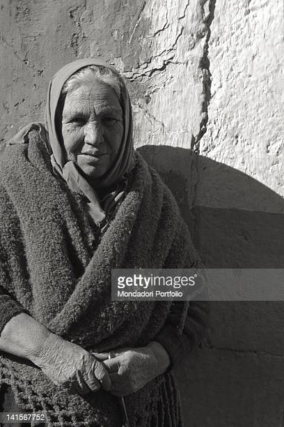 Closeup of an elderly woman from San Giovanni Rotondo resting against a wall Italy
