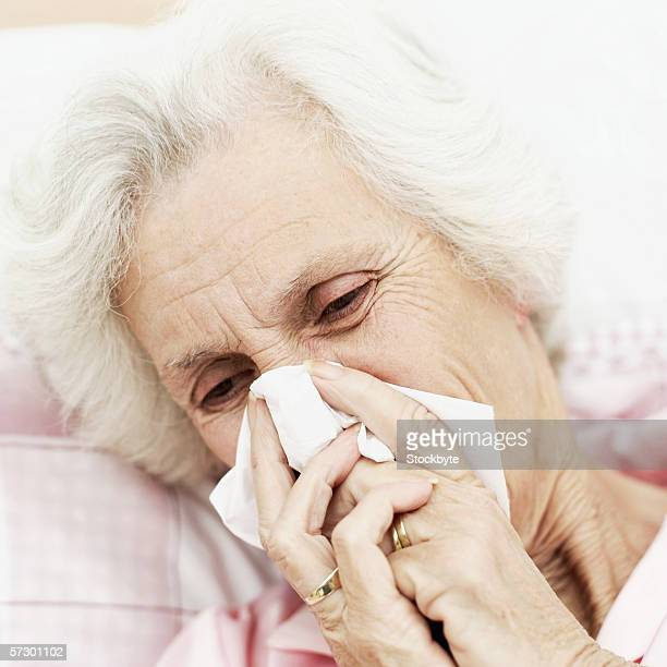 Close-up of an elderly woman lying in bed wiping her nose