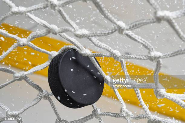 close-up of an ice hockey puck hitting the back of the net as snow flies, front view - hockey foto e immagini stock