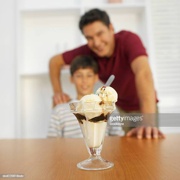 Close-up of an ice-cream with a father and son (11-12) in the background
