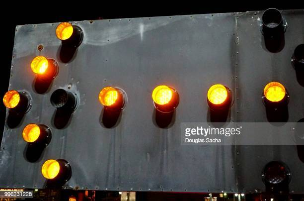 close-up of an illuminated arrow board traffic advisor panel - detour sign stock photos and pictures