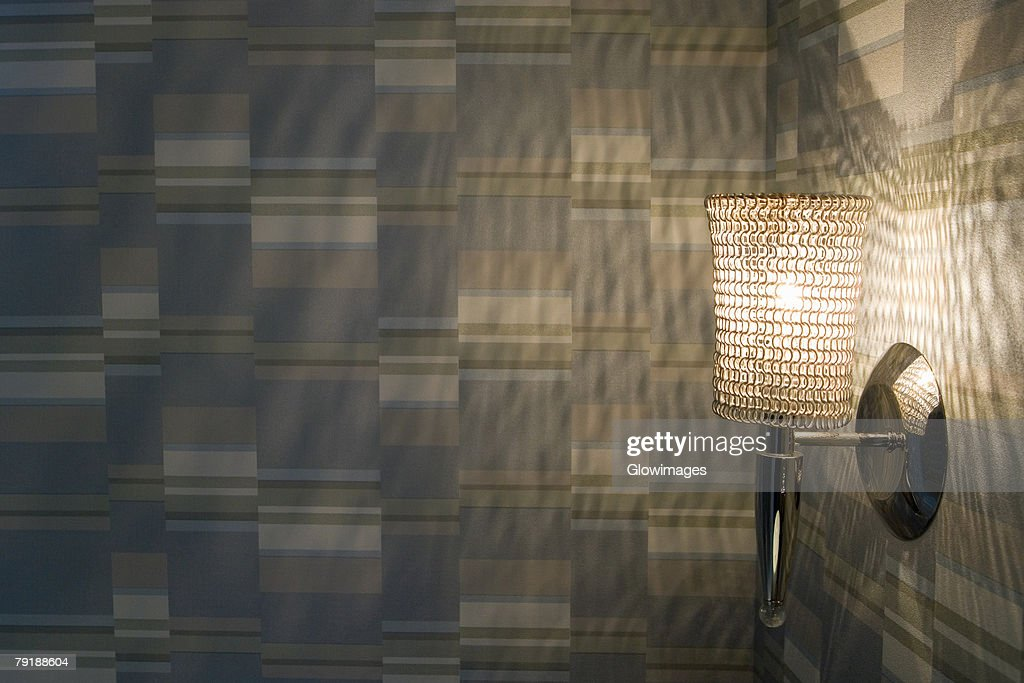 Close-up of an illuminated lamp on a wall : Stock Photo