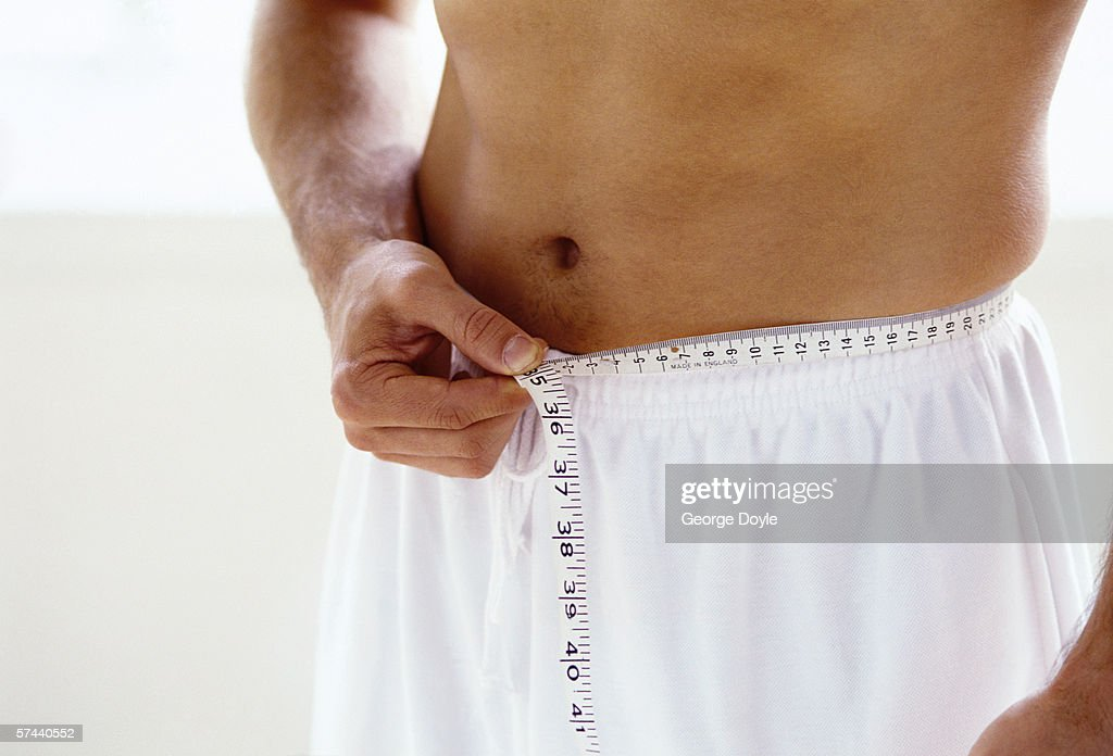 close-up of an inch tape wound around a man's waist : Stock Photo