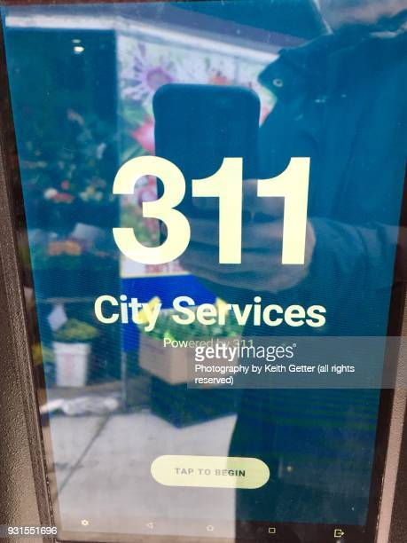 Close-up of an interactive kiosk in a smart city promoting '311' services
