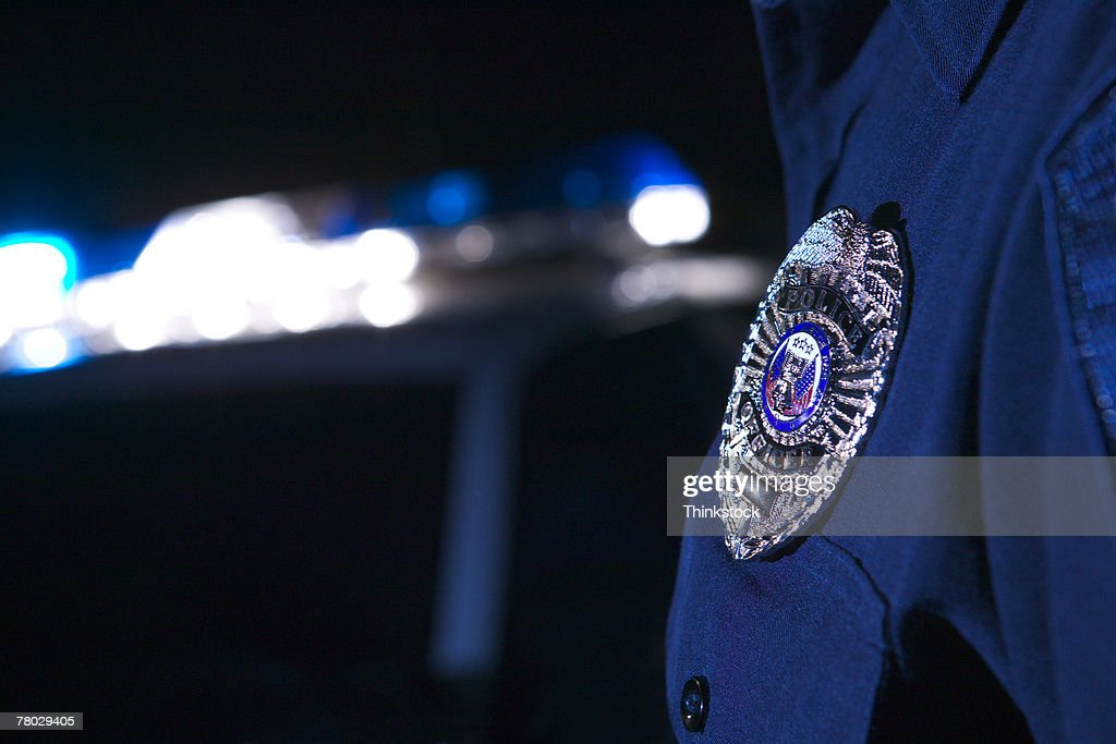 Close-up of an officer's badge with the police lights on the car flashing in the background : Stock Photo