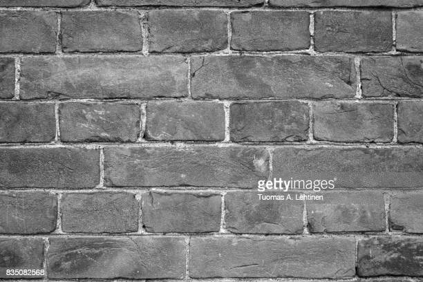 Close-up of an old and aged brick wall texture background with vignetting in black and white.