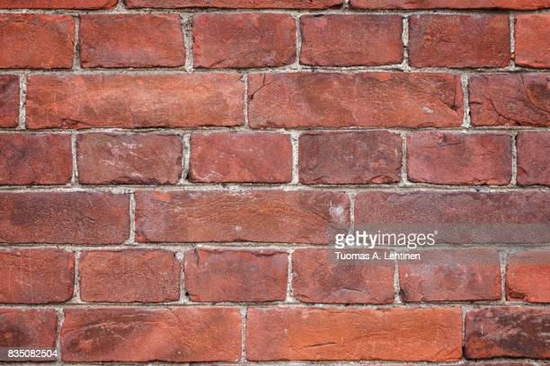 Close-up of an old and aged red brick wall texture background with vignetting.