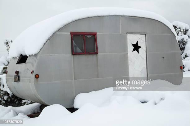 close-up of an old ham-can style travel trailer in the snow - timothy hearsum fotografías e imágenes de stock