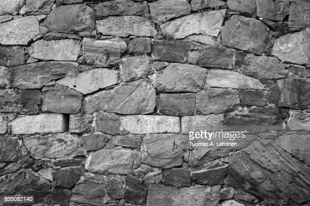 Close-up of an old surrounding wall at a fortress made of stones in black and white with vignetting.