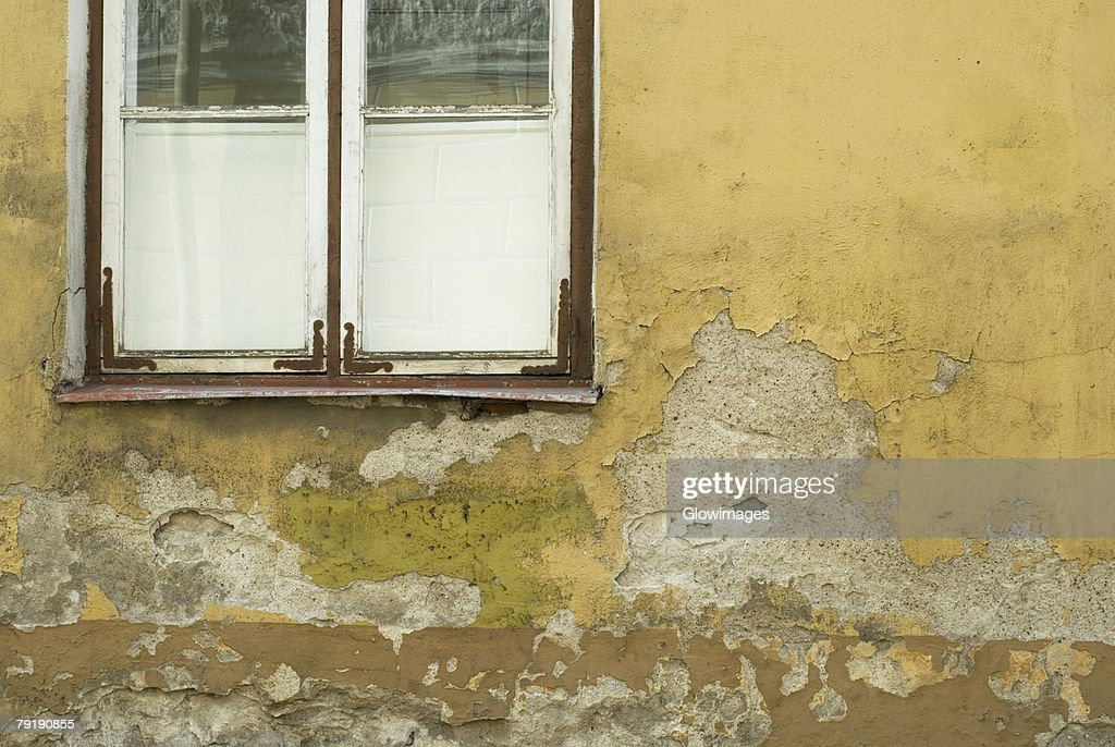 Close-up of an old window on a weathered wall : Foto de stock