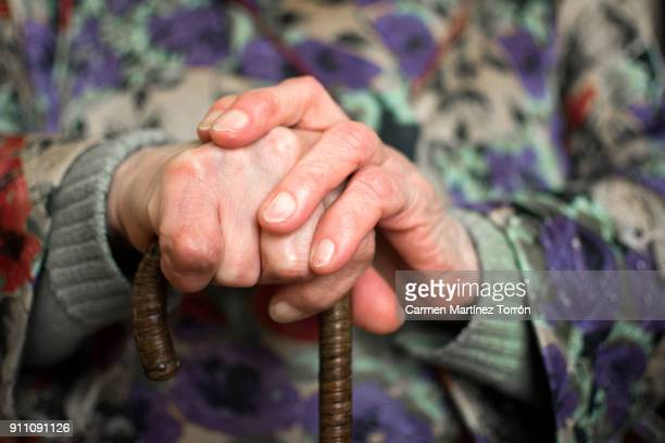 close-up of an old wrinkled hand holding a cane. - osteoarthritis stock photos and pictures