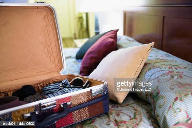 Close-up of an open suitcase and cushions on a bed