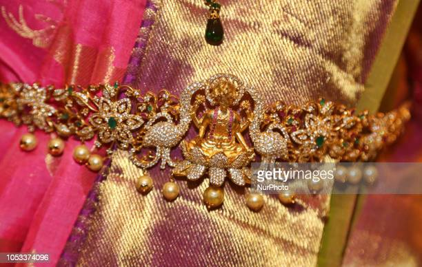 Close-up of an ornate belly chain with the figure of the Hindu Goddess Laxmi against an elegant sari during a South Asian bridal fashion show held in...