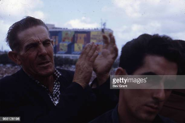 Closeup of an unidentified Cuban man as he applauds in the audience in la Plaza de la Revolucion during the 10th anniversary celebration of the Cuban...