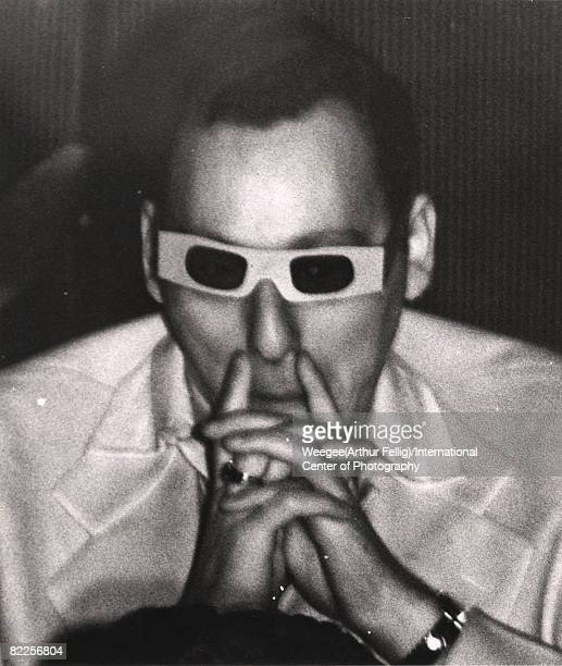 Closeup of an unidentified man as he watches a movie in 3D glasses his hands clasped at his chin a finger on each side of his nose New York New York...