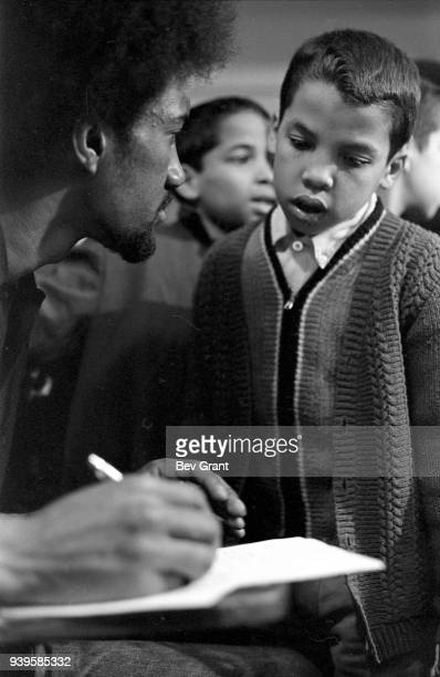 Closeup of an unidentified man as he writes in a notebook while talking to young boy during a free breakfast for children program sponsored by the...
