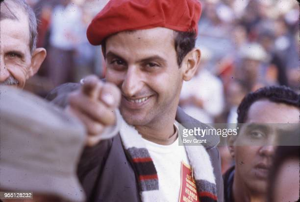 Closeup of an unidentified man in a red beret smiles as he points at the camera from the audience in la Plaza de la Revolucion during the 10th...