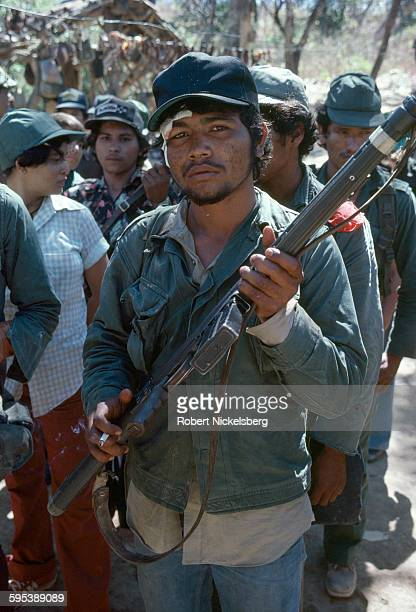 Closeup of an unidentified Popular Forces of Liberation guerrilla as he stands in formation with others at a camp near Santa Anita in Chalatenango...