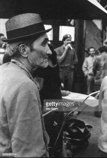Closeup of an unidentified street vendor as in the background Young Lords Party Minister of Education Carlos Aponte speaks to people on a Bronx...
