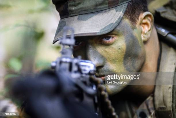 Closeup of an unidentified US Army Special Forces Sergeant as he looks along the barrel of a tripodmouted machine gun at Fort Bragg North Carolina...