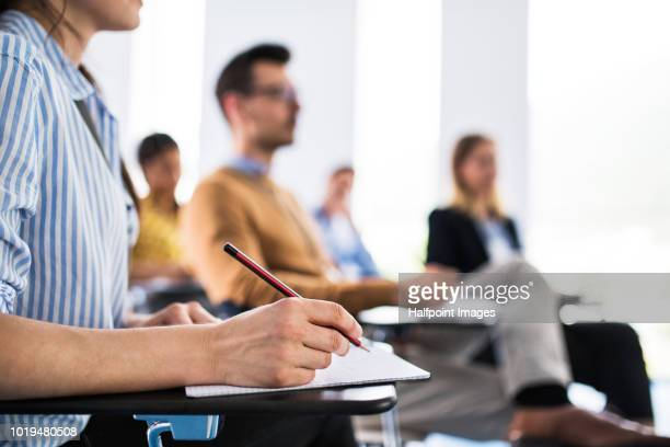 a close-up of an unrecognizable woman sitting in a board room,  making notes. - niveau de scolarisation photos et images de collection
