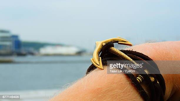 Close-Up Of Anchor Shaped Bracelet On Hand