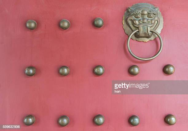 Close-up of Ancient Ornate Gold Handle, Knocker on Red Door in Chinese Temple