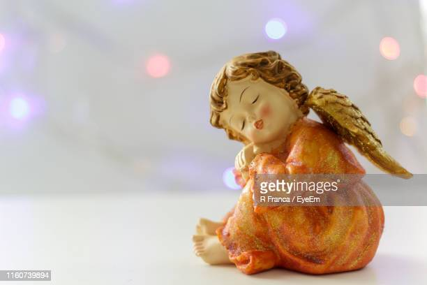 close-up of angel statue on table - angelo foto e immagini stock