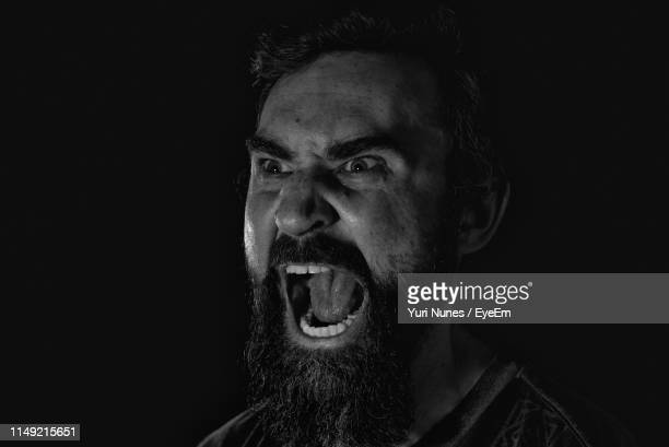 close-up of angry man shouting against black background - gritar fotografías e imágenes de stock