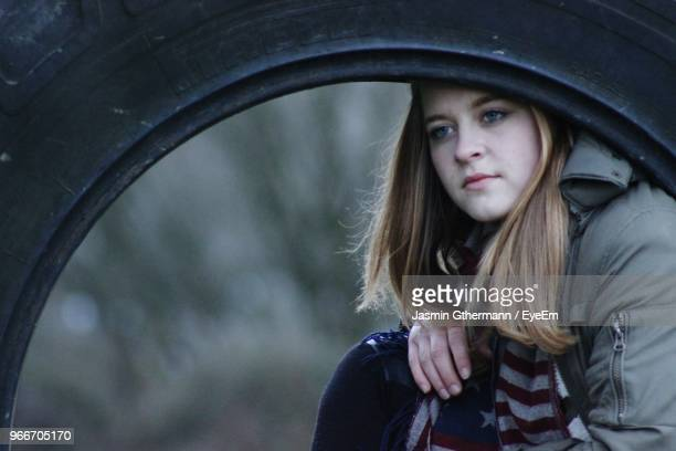 Close-Up Of Angry Woman Seen Through Tire