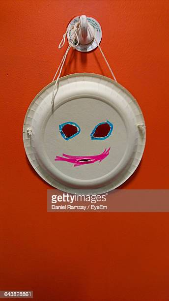 Close-Up Of Anthropomorphic Face On Paper Plate Against Red Background