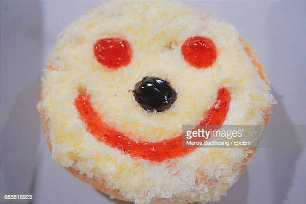 Close-Up Of Anthropomorphic Smiley Face Over Donut On Table
