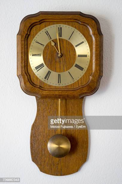 close-up of antique wall clock against white wall - wall clock stock photos and pictures