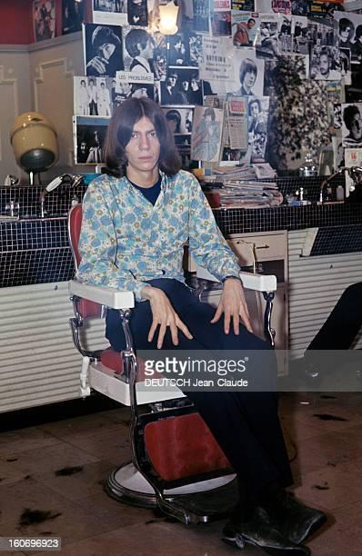 Closeup Of Antoine ANTOINE cheveux milongs vêtu d'une chemise à fleurs dans les tons bleu et vert pose assis sur le fauteuil d'un salon de coiffure...
