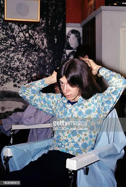 Closeup Of Antoine ANTOINE cheveux milongs vêtu d'une chemise à fleurs dans les tons bleu et vert passe ses mains à l'arrière de sa chevelure assis...
