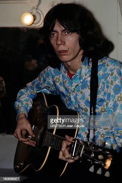 Closeup Of Antoine ANTOINE cheveux milongs vêtu d'une chemise à fleurs dans les tons bleu et vert joue de la guitare vue de profil