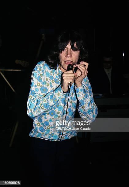 Closeup Of Antoine ANTOINE cheveux milongs vêtu d'une chemise à fleurs dans les tons bleu et vert chante au micro un harmonica à la main gauche