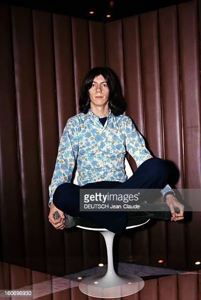 Closeup Of Antoine ANTOINE cheveux milongs vêtu d'une chemise à fleurs dans les tons bleu et vert pose assis en posture yoga 'lotus'
