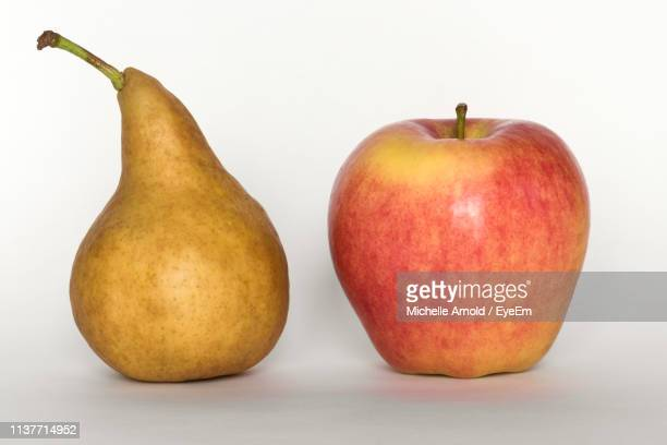 close-up of apple and pear against white background - maduro fotografías e imágenes de stock