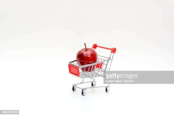 Close-Up Of Apple In Shopping Cart Against White Background
