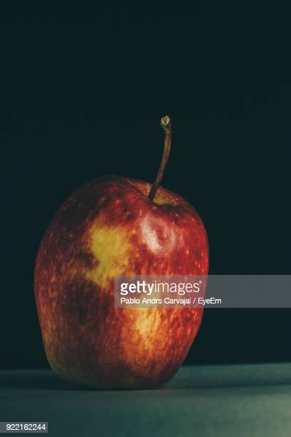 close-up of apple on table against black background - carvajal stock photos and pictures