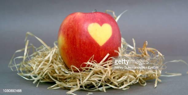 Close-Up Of Apple With Heart Shape And Hay On Gray Background