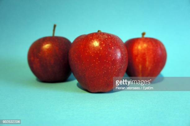 Close-Up Of Apples Against Colored Background
