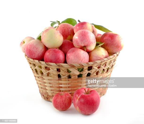 close-up of apples in basket against white background - basket stock pictures, royalty-free photos & images