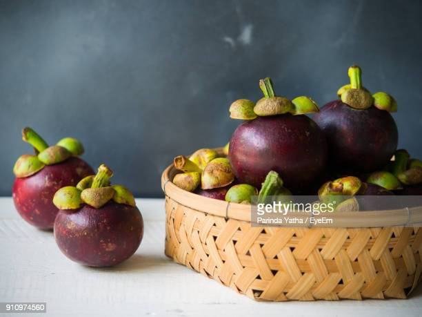 close-up of apples in basket on table - mangosteen stock photos and pictures
