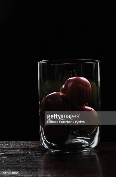 Close-Up Of Apples In Glass Vase On Table Against Black Background