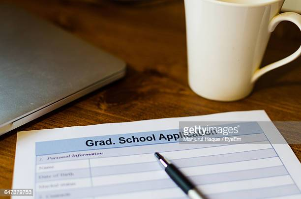 close-up of application form with coffee cup and pen on table - college application stock photos and pictures